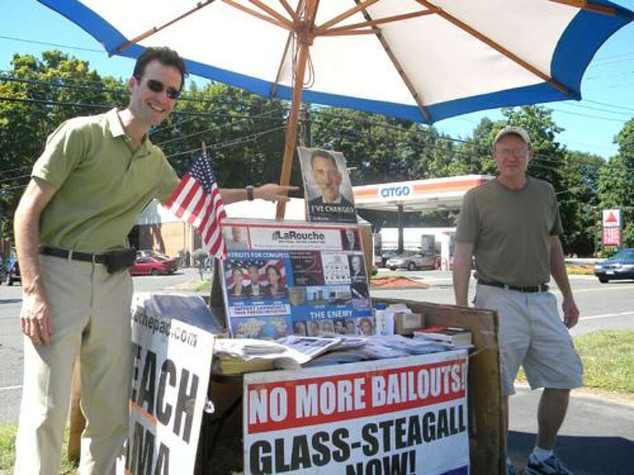 Jean-Sebastien Tremblay, left, of Philadelphia and Chris Sare of New Jersey stand beside their Impeach Obama stand Friday on Main Street in Cromwell. Photo by Justin Kloczko/Press Staff