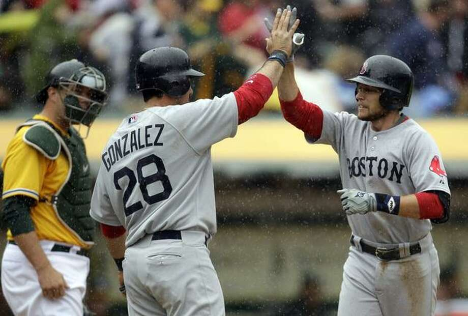 Boston Red Sox's Jed Lowrie, right, is congratulated by teammate Adrian Gonzalez after both scored on Lowrie's two-run home run off Oakland Athletics' Gio Gonzalez in the sixth inning of a baseball game, Wednesday, April 20, 2011, in Oakland, Calif. At left is A's catcher Landon Powell. (AP Photo/Ben Margot) Photo: ASSOCIATED PRESS / AP2011