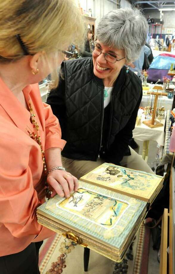 The Grass Island Flea Market at the former Mannix Motors building in Guilford. Debra Spencer left shows her friend Janice Gdovin right, both of Guilford, the scrapbooks Spencer makes with Gdovin's items that she sells at the market. (Photo by Mara Lavitt/Journal Register News Service 4/10/11)
