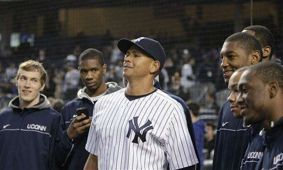 Connecticut basketball players watch as New York Yankees third baseman Alex Rodriguez, center, stretches to make himself reach their height before the Yankees' baseball game against the Baltimore Orioles at Yankee Stadium on Wednesday, April 13, 2011 in New York. (AP Photo/Kathy Willens) Photo: AP / AP