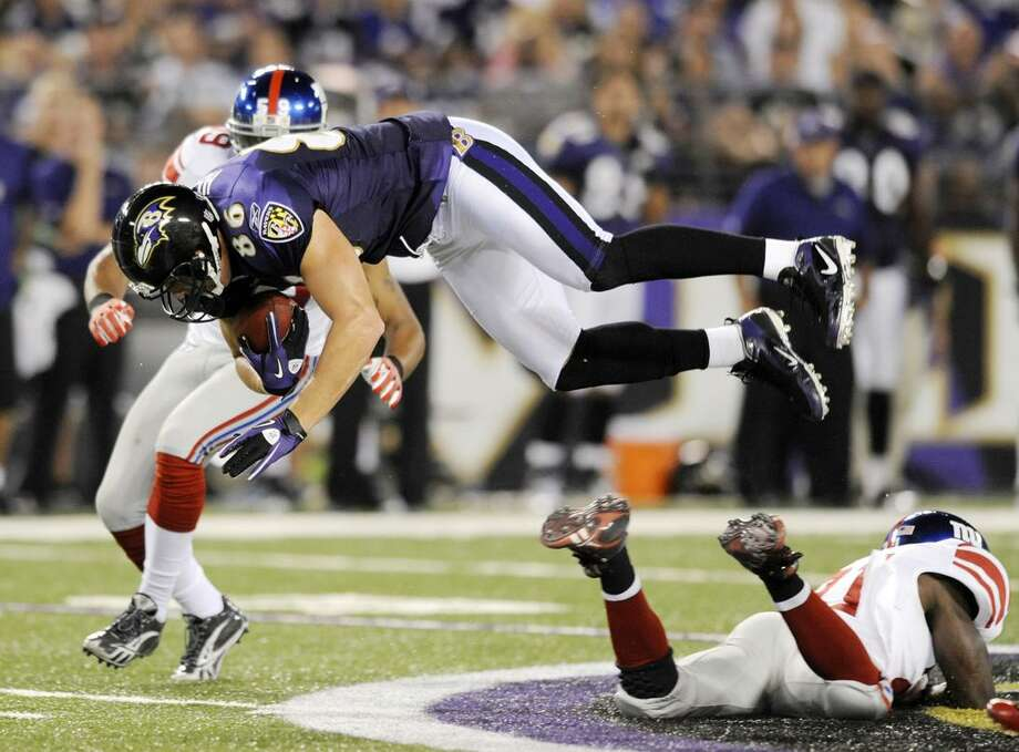 Baltimore Ravens tight end Todd Heap (86) is upended by New York Giants safety Kenny Phillips, right, during the first half of an NFL preseason football game, Saturday in Baltimore. At left is the Giants Michael Boley. (AP Photo/Gail Burton) Photo: AP / FR4095 AP