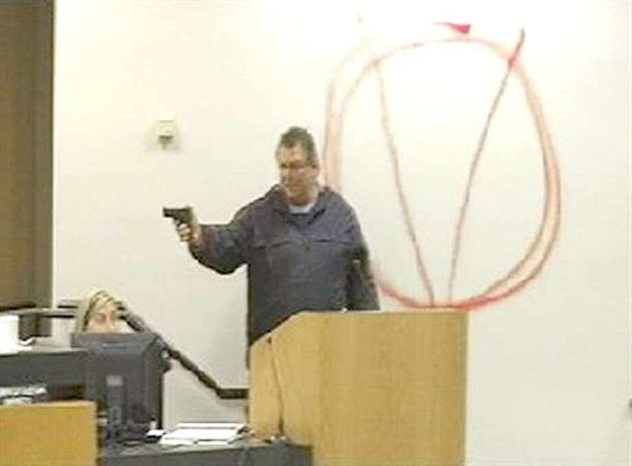 In this image taken from video and released by WJHG-TV, Clay A. Duke points a hand gun at Bay City school board members and staff, Tuesday, Dec. 14, 2010. Duke, a 56-year-old ex-convict, calmly held the school board at gunpoint and said he was seeking redress for his wife's firing before shooting at the superintendent at short range and then killing himself. (AP Photo/WJHG-TV) MANDATORY CREDIT Photo: AP / WJHG-TV