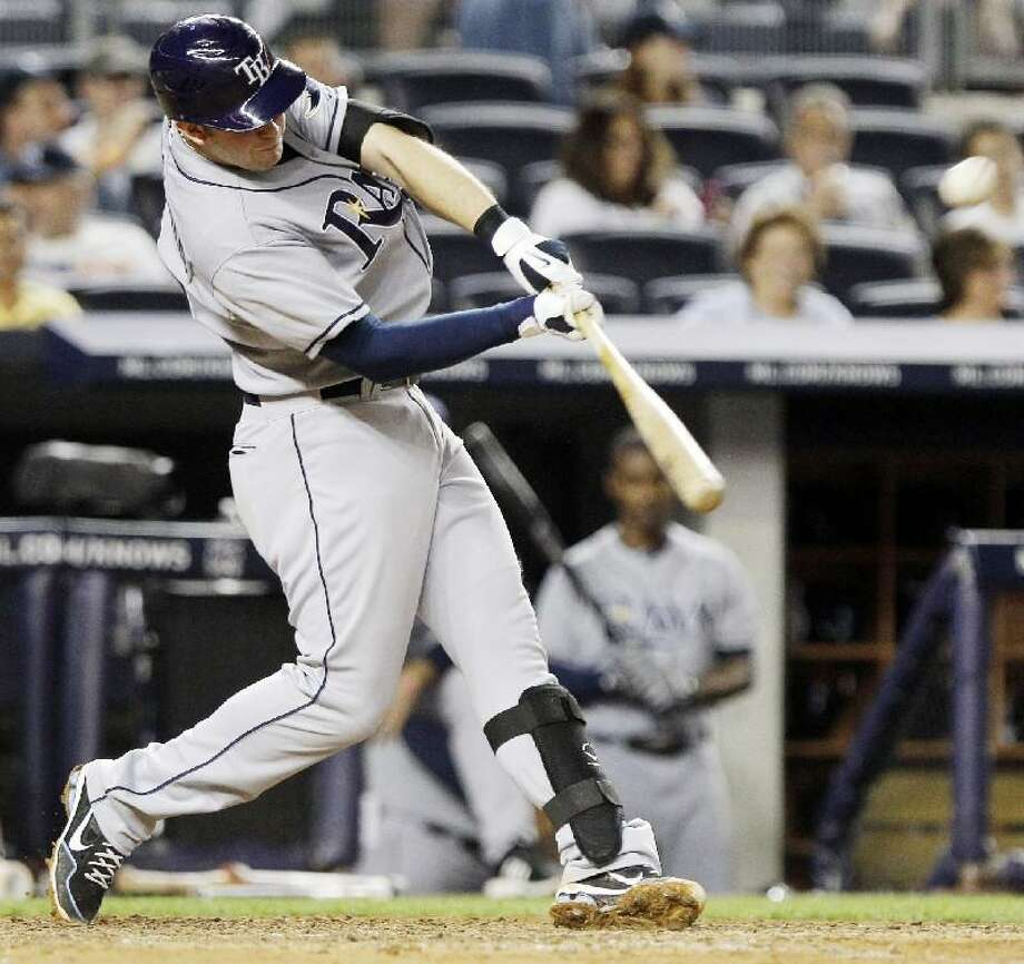 ASSOCIATED PRESS Tampa Bay Rays third baseman Evan Longoria hits a home run during the eighth inning of Friday nights's game against the New York Yankees at Yankee Stadium in New York. The Rays won the game 5-1. The Rays hit five solo home runs off of CC Sabathia in the game.