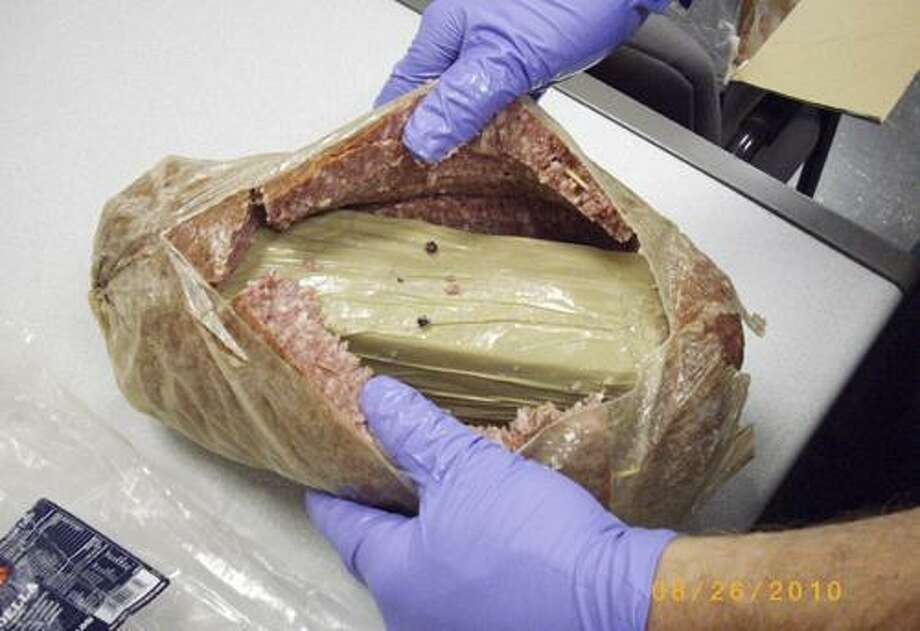In this Aug. 26, 2010 photo released by the Holyoke, Mass., police, an official reveals a package containing a kilogram of cocaine hidden inside a hollowed out chunk of bologna. Police arrested Juan Rodriguez Thursday when he received a package shipped from Puerto Rico to his Holyoke home that contained the cocaine and bologna.  (AP Photo/Holyoke Police Department) Photo: AP / Holyoke Police Department
