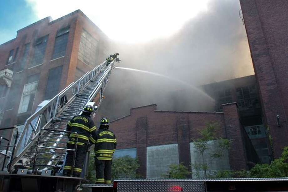 Firefighters with Ladder 11 battle a fire at the former Remington Arms plant, in Bridgeport, Conn. Saturday, Aug. 28th, 2010. The empty factory complex has been the site of numerous fires over the past several years. (AP Photo/The Connecticut Post, Ned Gerard) Photo: AP / Connecticut Post