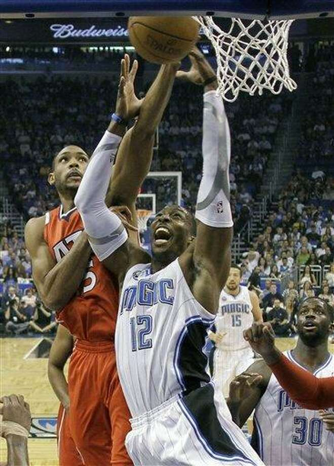 Orlando Magic's Dwight Howard (12) goes up for a rebound against Atlanta Hawks' Al Horford, left, during the first half of Game 1 of a first-round NBA playoff basketball series in Orlando, Fla., Saturday, April 16, 2011. (AP Photo/John Raoux) Photo: AP / AP
