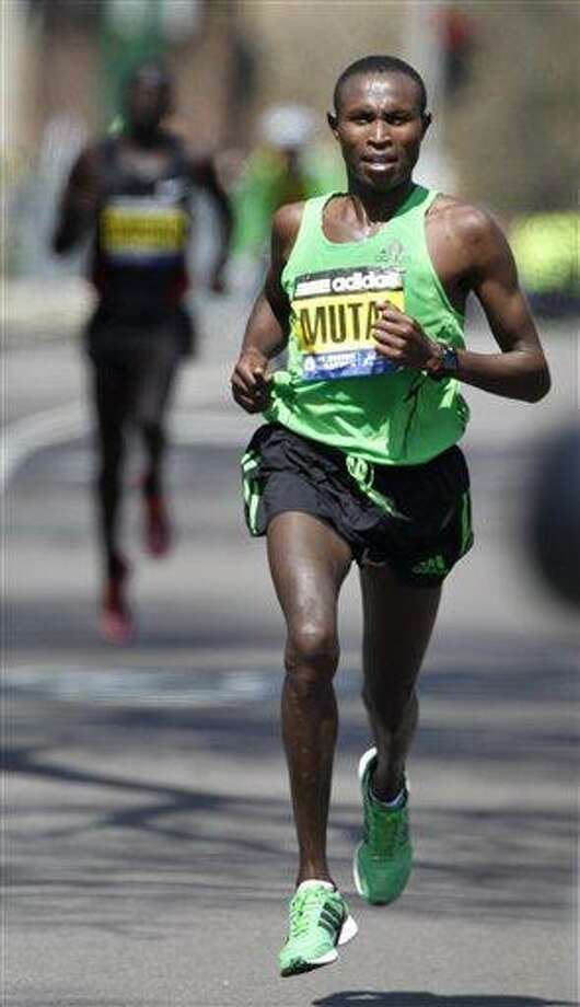 Geoffrey Mutai, right, runs ahead of Moses Mosop, left, both of Kenya, in the final miles of the Boston Marathon, in Boston, Monday, April 18, 2011,  Mutai went on to win the race. (AP Photo/Steven Senne) Photo: AP / AP