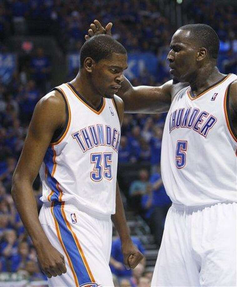 Oklahoma City Thunder forward Kevin Durant, left, and center Kendrick Perkins, right, celebrate after a basket by Durant in the third quarter of an NBA playoff basketball game against the Denver Nuggets in Oklahoma City, Sunday, April 17, 2011. Oklahoma City won 107-103. (AP Photo/Sue Ogrocki) Photo: ASSOCIATED PRESS / AP2011