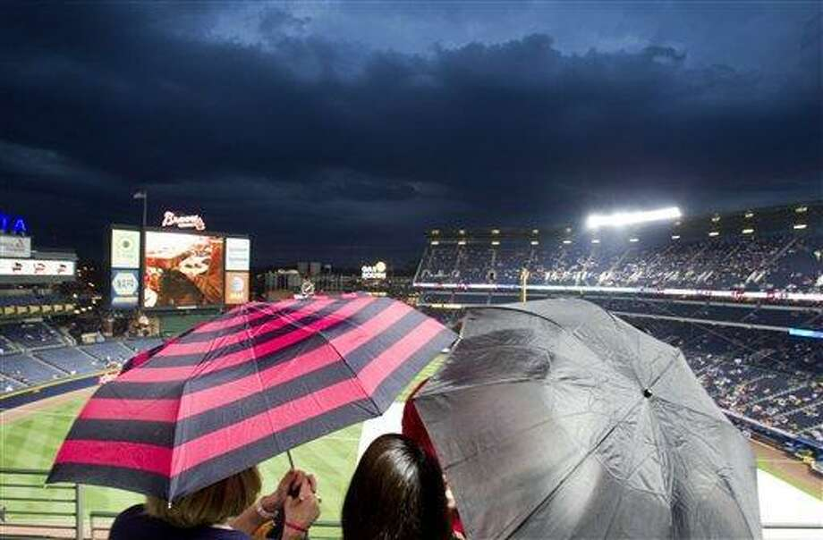 Fans huddle under umbrellas during a rain delay before a baseball game between the New York Mets and the Atlanta Braves was called due to weather on Friday, April 15, 2011, in Atlanta. (AP Photo/David Goldman) Photo: AP / AP