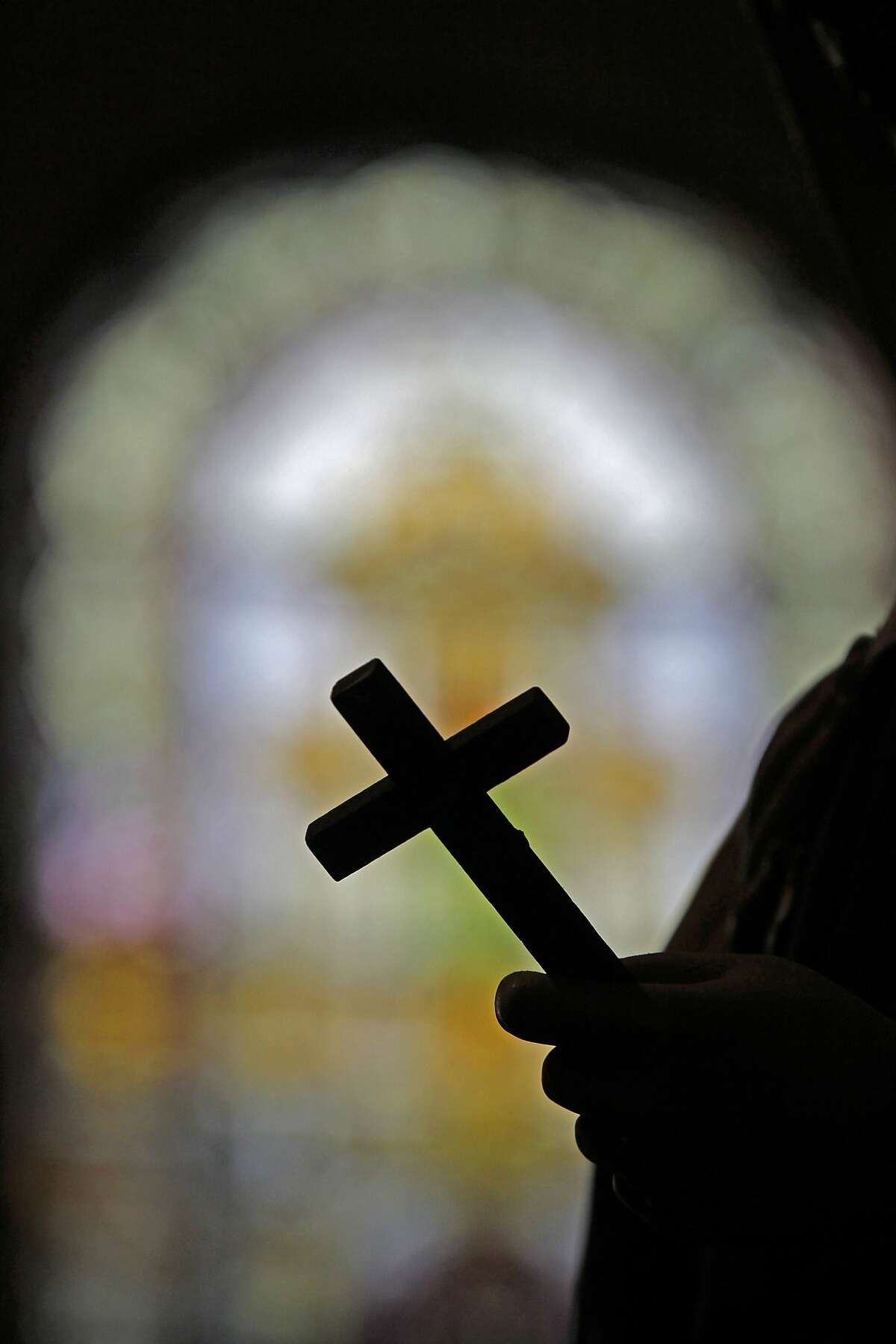 In this Dec. 1, 2012 photo, a silhouette of a crucifix and a stained glass window is seen inside a Catholic Church in New Orleans. Catholic groups are decrying a recent Louisiana Supreme Court decision that reaches into the most sanctified of Catholic places, the confessional booth. The high court has revived a sex abuse lawsuit in which parents are suing a priest and a local diocese for not reporting the alleged abuse when the teenager told the priest about it, and the ruling could have a priest asked to testify about what was said in a private confession. The Catholic League for Religious and Civil Rights says the ruling leaves the priest choosing between prison and excommunication, in a case that has grabbed attention in heavily Catholic south Louisiana. (AP Photo/Gerald Herbert)