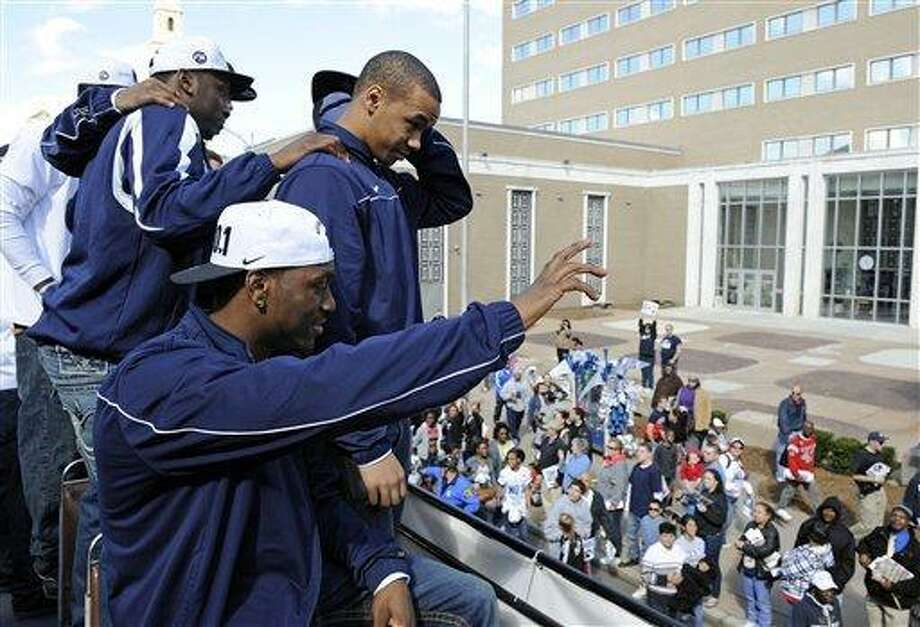 Members of Connecticut's 2011 national champion men's basketball team celebrate aboard a double-decker bus during a victory parade in Hartford, Conn., on Sunday, April 17, 2011. (AP Photo/Fred Beckham) Photo: AP / FR153656 AP