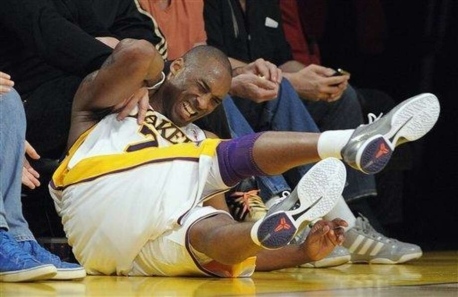 Los Angeles Lakers guard Kobe Bryant reacts after falling an d hitting his neck on a chair during the first half of an NBA playoff basketball game against the New Orleans Hornets, Sunday, April 17, 2011, in Los Angeles.  (AP Photo/Mark J. Terrill) Photo: ASSOCIATED PRESS / AP2011