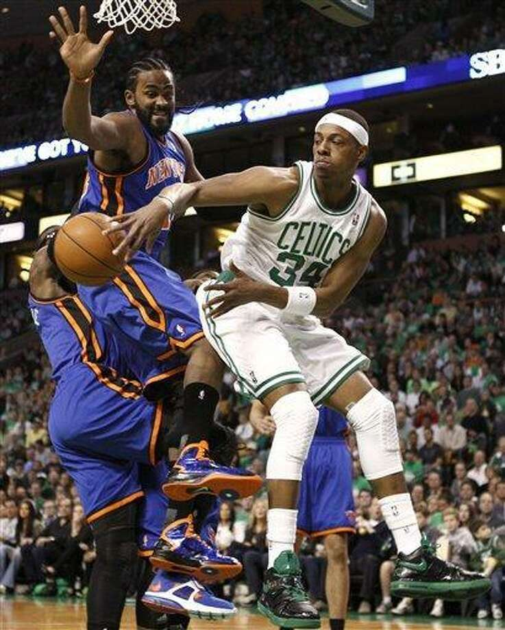Boston Celtics' Paul Pierce (34) passes around New York Knicks' Ronny Turiaf during the first quarter in Game 1 of a first-round NBA basketball playoff series, in Boston on Sunday, April 17, 2011. (AP Photo/Winslow Townson) Photo: AP / FR170221 AP