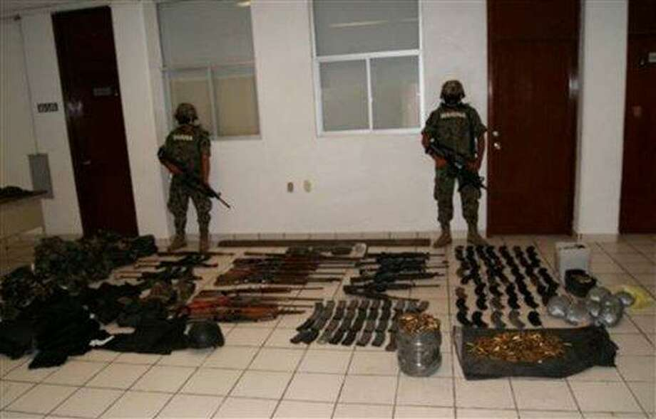 In this image released by Mexico's Navy, mexican Navy sailors guard the weapons seized after a gun fight between the navy and drug cartel gunmen after the killing of 72 migrants in San Fernando, eastern Mexico, Tuesday, Aug. 24, 2010. A Mexican drug cartel massacred 72 Central and South American migrants within 100 miles of the U.S. border that they were trying to reach, according to Lala Pomavilla who said to be a survivor who escaped and stumbled wounded to a highway checkpoint where he alerted marines. Lala Pomavilla told investigators that his captors identified themselves as members of the Zetas drug gang, said Vice Adm. Jose Luis Vergara, a spokesman for the Mexican Navy. (AP Photo/ Mexico's Secretary Navy) Photo: AP / AP