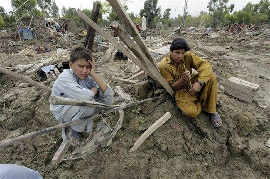 Pakistani villagers sit over their houses collapsed by floods in Nowshera, Pakistan, Thursday, Aug. 26, 2010. Pakistani officials urged anyone left in three southern towns Thursday to evacuate immediately as floodwaters broke through a levee, endangering areas previously untouched by the country's almost monthlong disaster. (AP Photo/Mohammad Sajjad) Photo: AP / AP