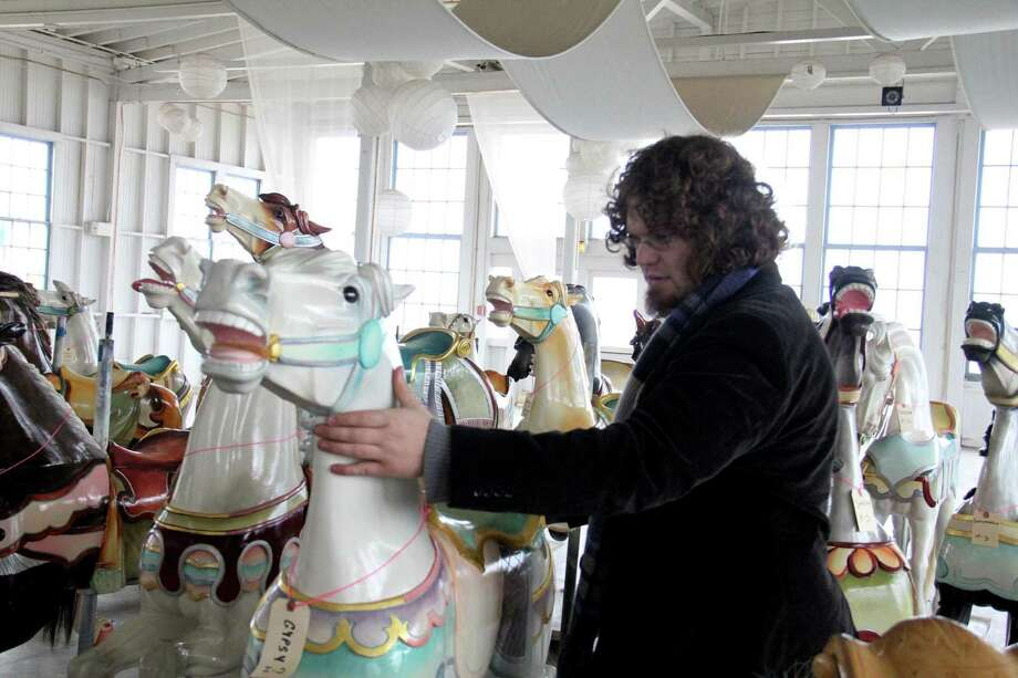 New Haven-- Gabe Finkenstein son of owner Bill Finkenstein owner of WRF Designs located in Plainville, CT looks over one of 27 restored carousel horses at Lighthouse Point Park Thursday in New Haven. Photo by NeRonda   Langley-03.31.11 (Journal Register News Service)