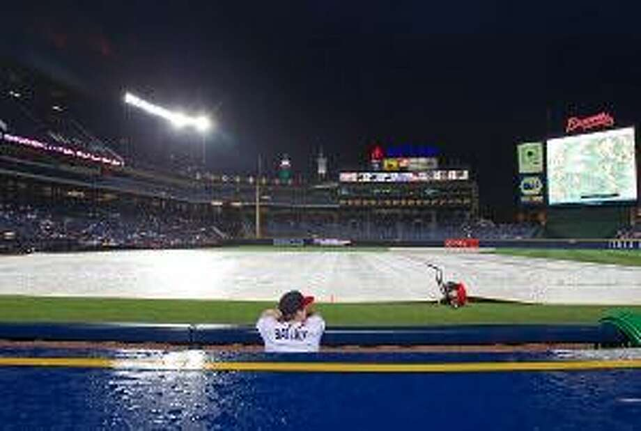 AP A bat boy looks the weather radar, right, during a rain delay before a game between the New York Mets and the Atlanta Braves was eventually called due to weather on Friday in Atlanta.
