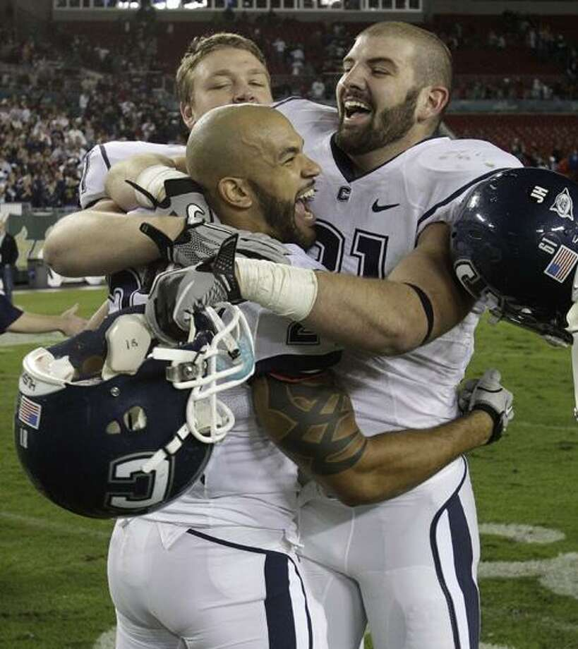Connecticut running back D.J. Shoemate (24) celebrates with teammates Stephen Brown (61) and Jesse Joseph (91) after defeating South Florida 19-16 to clinch the Big East Conference title during an NCAA college football game Saturday, Dec. 4, 2010, in Tampa, Fla. (AP Photo/Chris O'Meara) Photo: ASSOCIATED PRESS / AP2010