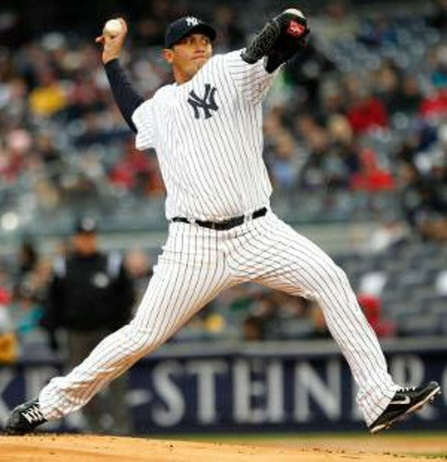 AP New York's Freddy Garcia delivers a pitch during the first inning of Saturday's game against the Texas Rangers at Yankee Stadium in New York. The Yankees won 5-2.