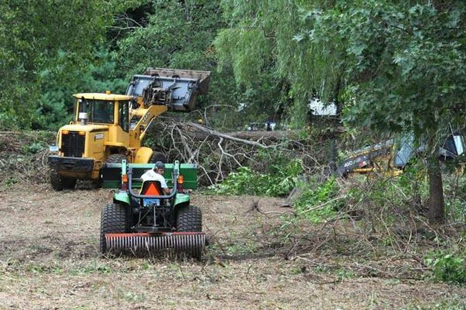 Employees of the Branford Public Works Department clear brush along the tree line on the cove side of Parker Memorial Park in Branford Tuesday. Police said the work was part of a search for evidence in an old case, but would not reveal the nature of the crime. (VM Williams/Register photos)