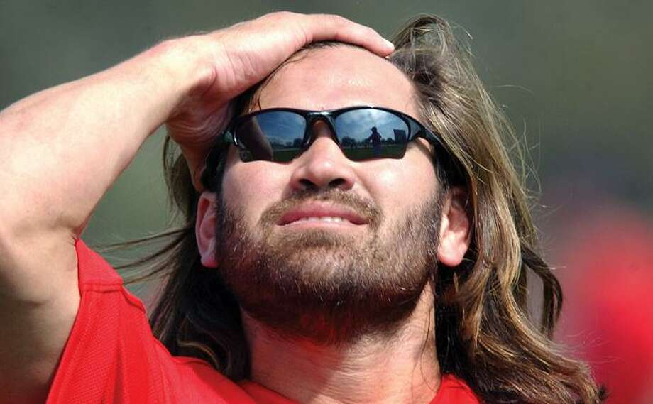 Boston Red Sox outfielder Johnny Damon pulls back his hair before donning his cap Monday, Feb. 21, 2005, during a spring training workout in Fort Myers, Fla. The 36-year-old outfielder decided to pass up a chance to return to the Boston Red Sox, rejecting their waiver claim and choosing to remain with the Detroit Tigers. (AP)