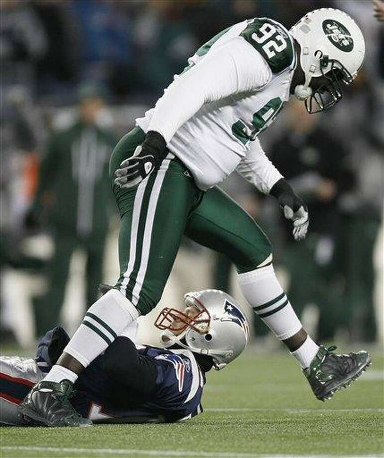 FILE - This Jan. 16, 2011, file photo shows New York Jets defensive end Shaun Ellis stepping over New England Patriots quarterback Tom Brady after sacking him during the first half of an NFL divisional playoff football game in Foxborough, Mass.  Ellis is switching sides in one of the NFL's most intense rivalries.The two-time Pro Bowl selection signed with the New England Patriots on Monday, Aug. 8, 2011,  after 11 seasons with the New York Jets. (AP Photo/Winslow Townson, File) Photo: ASSOCIATED PRESS / AP2011