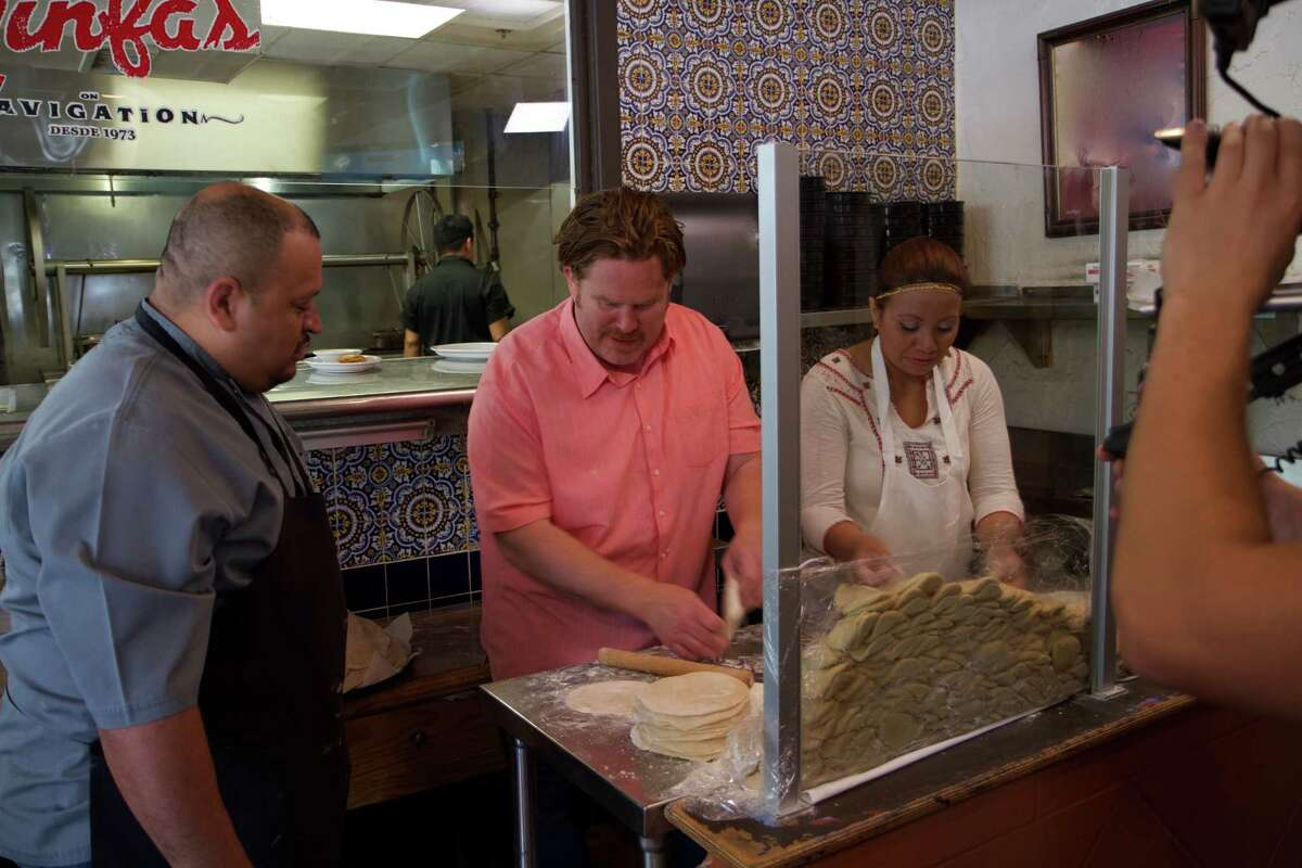 """Host Casey Webb of Travel Channel's """"Man v. Food,"""" learns how to make tortillas from scratch with Ninfa's On Navigation's kitchen staff in Houston."""