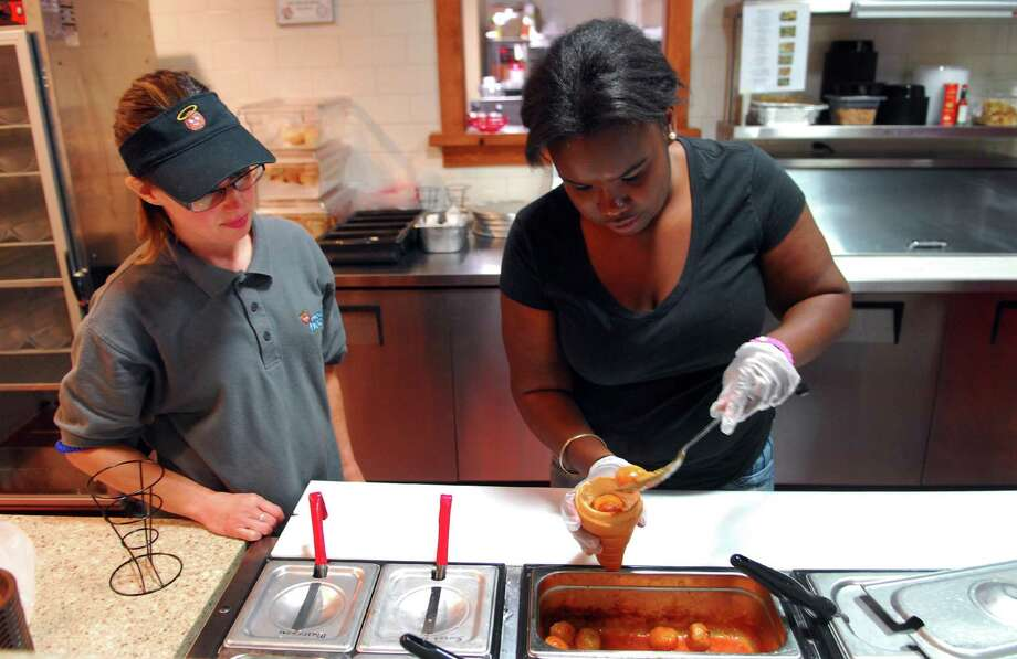 Boys and Girls Village's Work to Learn Program Manager BethAnn Jackson, left, supervises a program participant to prepare a meal at Meatball Heaven, located inside the Arcade Mall on Main Street in downtown Bridgeport. Photo: Christian Abraham / Hearst Connecticut Media / Connecticut Post