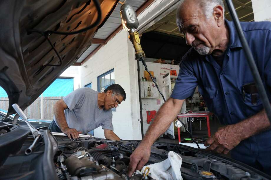 Khosrow Askandari and Sammy Sibouyen, of K&R Auto, replace a faulty fuel injector on a 2009 Toyota Corolla and clean grime off its headlights. Photo: Mike Morris, Houston Chronicle