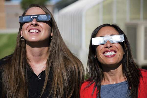 Science teachers Ashley Moretti, left, and Candace Wright, right, use their eclipse shades to look at the sun as they pose for a portrait at Twin Falls High School in Twin Falls, Idaho. The district bought 11,000 pairs of solar glasses, enough for every student and staff member to view the solar eclipse Aug. 21, from Twin Falls.