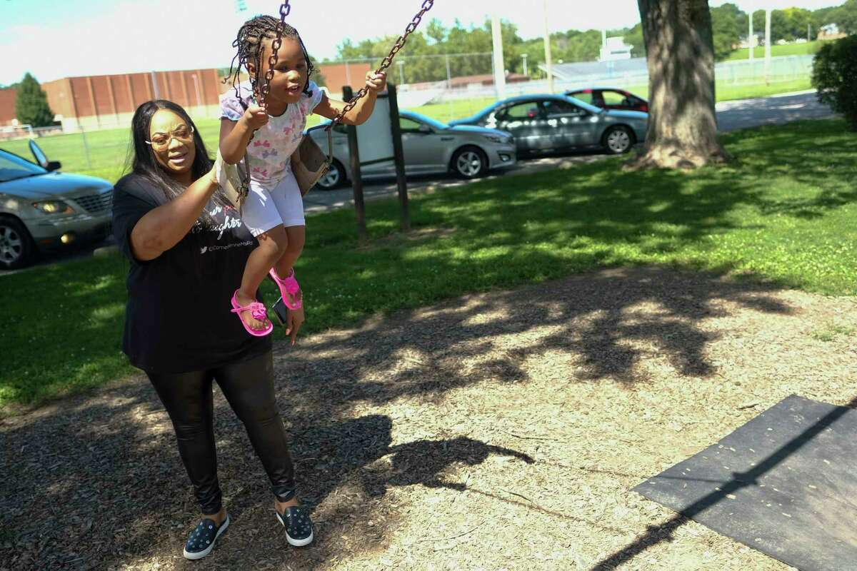 Ms. Pat pushes one of her granddaughters on a swing. mUST CREDIT: Photo by AJ Mast for the Washington Post.