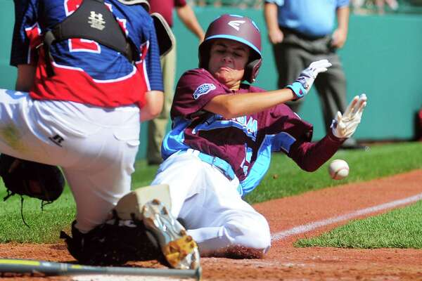 Fairfield American's Andrew Cutler slides into home plate as Mid-Atlantic's J.R. Osmond receives the ball during Little League World Series action at Lamade Stadium in South Williamsport, Penn., on Thursday Aug. 17, 2017. Osmond missed the ball allowing Cutler to score.