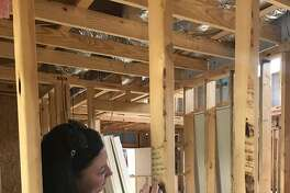 Emily Gonzales with Lennar/Village Builders writes words of encouragement and inspiration on the cottage being constructed by HomeAid and Lennar/Village for eight boys and their teaching parents.