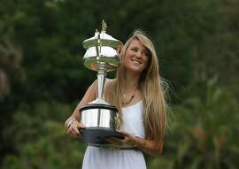 Victoria Azarenka of Belarus poses with the Australian Open trophy in the Royal Botanical Gardens following her win over China's Li Na in the women's final, in Melbourne, Australia, Sunday, Jan. 27, 2013. (AP Photo/Aaron Favila)