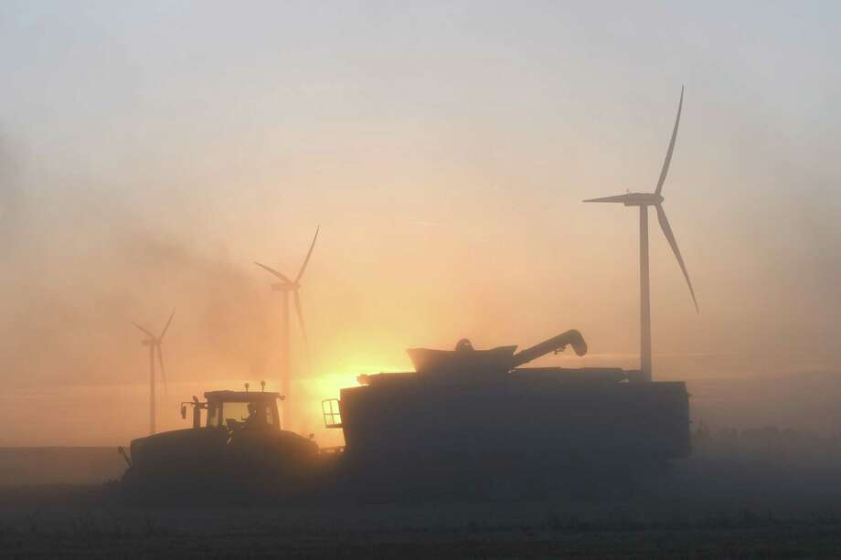 A French farmer harvests a wheat field with a combine harvester, next to wind turbines, on a wind farm in Rouvray-Saint-Florentin, central France. Climate change will have a negative effect on key crops such as wheat, rice, and maize, as the world experiences more hot days, fewer cool nights and other deleterious effects from emissions humans release into the atmosphere. Photo: JEAN-FRANCOIS MONIER /AFP /Getty Images / AFP or licensors