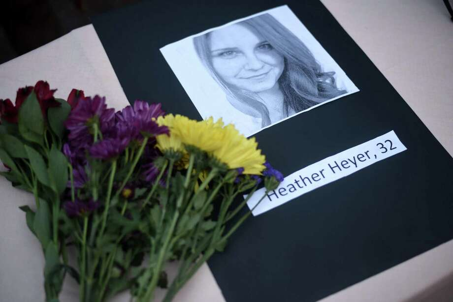A portrait of Heather Heyer, who was killed when a vehicle drove through counter protestors in Charlottesville, Va., lies on a table with flowers during a vigil on the campus of the University of Southern Mississippi in Hattiesburg, Miss. on Monday. Photo: Courtland Wells /Associated Press / The Vicksburg Post