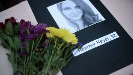 A portrait of Heather Heyer, who was killed when a vehicle drove through counter protestors in Charlottesville, Va., lies on a table with flowers during a vigil on the campus of the University of Southern Mississippi in Hattiesburg, Miss. on Monday.