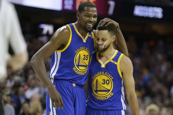 FILE - In this Friday, June 9, 2017, file photo, Golden State Warriors' Kevin Durant (35) hugs teammate Stephen Curry (30) during the first half of Game 4 of basketball's NBA Finals against the Cleveland Cavaliers, in Cleveland. The 2017 NBA Champion Golden State Warriors re-signed free agents Stephen Curry, Kevin Durant, Andre Iguodala, Shaun Livingston, Zaza Pachulia and David West to contracts, the team announced Tuesday, July 25, 2017. (AP Photo/Tony Dejak, File)
