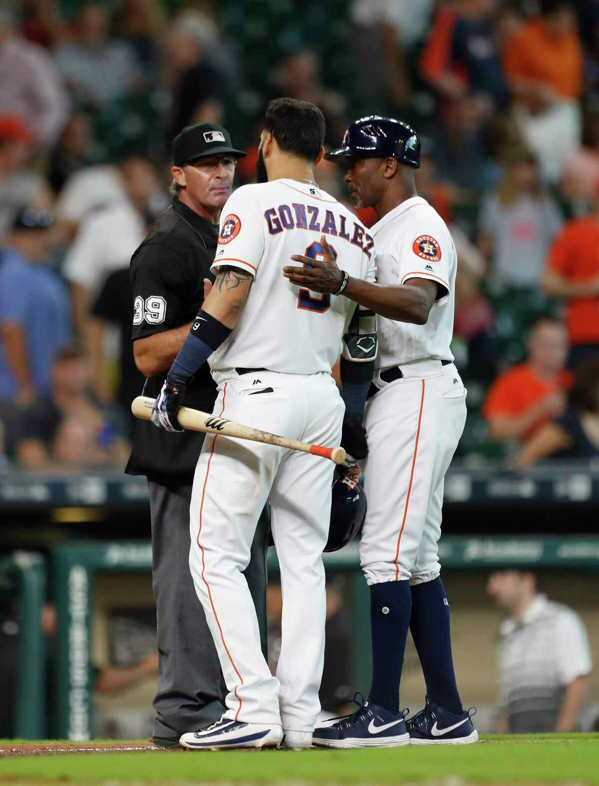 Houston Astros third base coach Gary Pettis (8) tries to pull Marwin Gonzalez (9) away as he argued with home plate umpire Paul Nauert after striking out to end in the game during an MLB game at Minute Maid Park, Thursday, Aug. 17, 2017, in Houston.