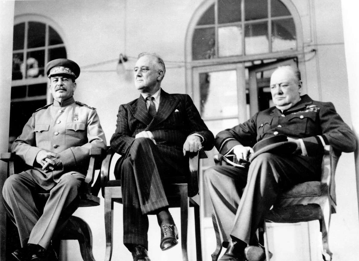 In this Nov. 28, 1943 file photo, Soviet Union Premier Josef Stalin, U.S. President Franklin D. Roosevelt, center, and British Prime Minister Winston Churchill sit together during the Tehran Conference in Tehran, Iran. The three leaders, meeting for the first time, discussed Allied plans for the war against Germany and for postwar cooperation in the United Nations.