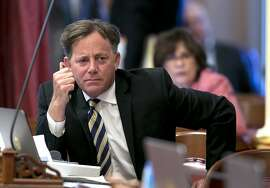 FILE -- In this June 15, 2017 file photo state Sen. Josh Newman, D-Fullerton, listens as lawmakers debate a measure to change the rules governing recall elections, at the Capitol, in Sacramento, Calif. Records show that an attorney for Senate Democrats spoke behind the scenes with Fair Political Practices Commission member Brian Hatch before the commission voted change a longstanding rule that restricts how much money Newman can raise from fellow lawmakers to fight a recall.(AP Photo/Rich Pedroncelli, file)