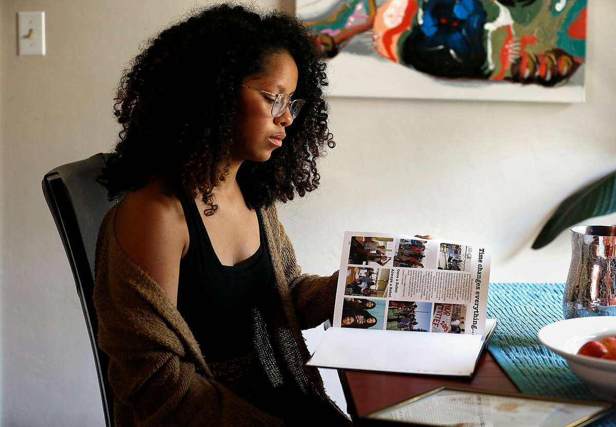 Naliyah Martinez-Truso, 17 years old, who recently graduated from San Lorenzo High School goes through her yearbook and school memorabilia showing rebel and confederate mascots on Thursday, August 17, 2017, in Vallejo, Calif.