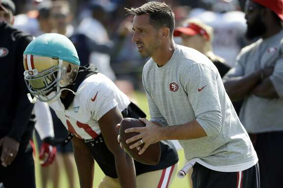 San Francisco 49ers head coach Kyle Shanahan, right, prepares to throw during a joint NFL football practice with the Denver Broncos Wednesday, Aug. 16, 2017, in Santa Clara, Calif. (AP Photo/Marcio Jose Sanchez)