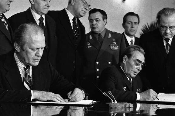 """President Ford and Soviet General Secretary Leonid I. Brezhnev sign a Joint Communiqu following talks on the limitation of strategic offensive arms. The document was signed in the conference hall of the Okeansky Sanitarium, Vladivostok, USSR. November 24, 1974. Former President Gerald R. Ford, who declared """"Our long national nightmare is over"""" as he replaced Richard Nixon but may have doomed his own chances of election by pardoning his disgraced predecessor, has died Tuesday Dec. 26, 2006. He was 93. (AP Photo/White House Photograph Courtesy Gerald R. Ford Library)"""