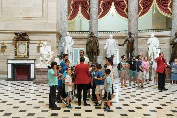 A tour in front of statues, including that of Confederate president Jefferson Davis, third from left (it is the bronze statue in the middle here), in Statuary Hall of the Capitol Building in Washington. Rep. Nancy Pelosi urged the removal of Confederate statues from the Capitol.