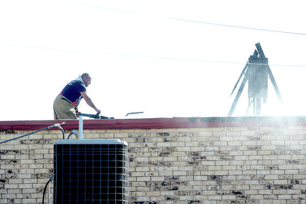 Firefighters continue to monitor the scene of a fire at the Snooper's Paradise shopping strip in Groves Thursday. A nearby worker alerted area responders to heavy smoke coming from the back of the large retail building, which still houses a few small businesses. Crews from several departments were called in to assist as back-up for precautionary reasons due to the size of the building and proximity to a nearby apartment complex.  Photo taken Thursday, August 17, 2017 Kim Brent/The Enterprise