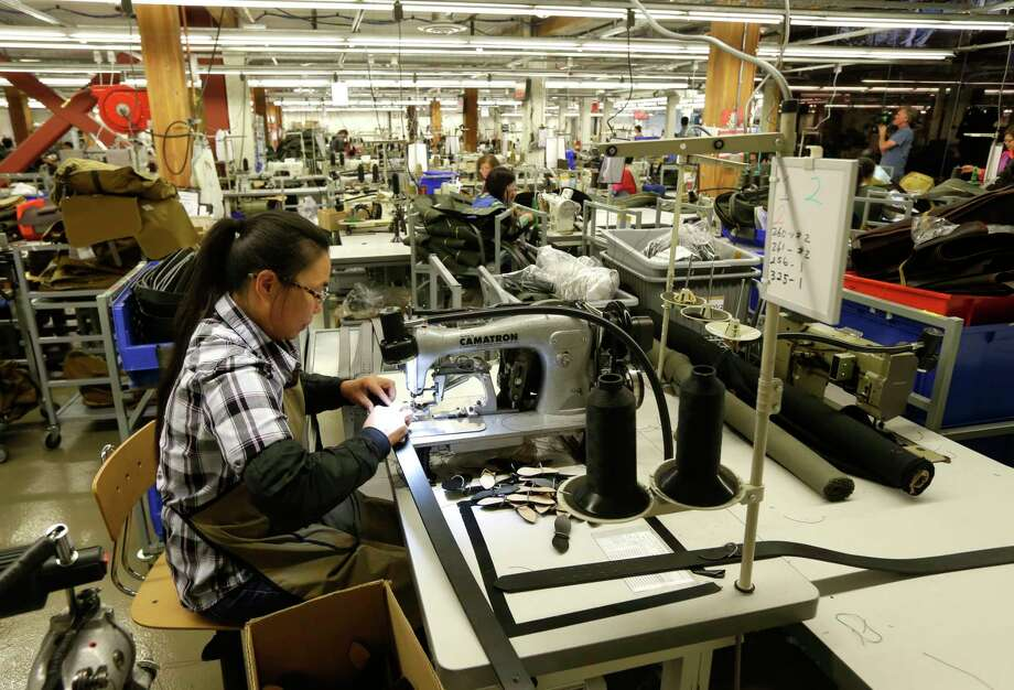 A worker at the C.C. Filson Co. manufacturing plant  stitches a belt at a sewing machine in Seattle. U.S. factory production fell 0.1 percent last month. Photo: Ted S. Warren, STF / Copyright 2017 The Associated Press. All rights reserved.