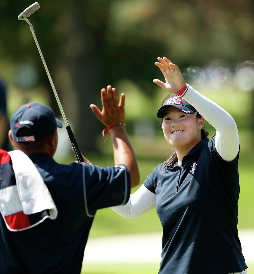 United States' Angel Yin celebrates with her caddie after making a putt on the eighth green during practice for the Solheim Cup golf matches, Thursday, Aug. 17, 2017, in West Des Moines, Iowa. (AP Photo/Charlie Neibergall) ORG XMIT: IACN128 Photo: Charlie Neibergall / Copyright 2017 The Associated Press. All rights reserved.