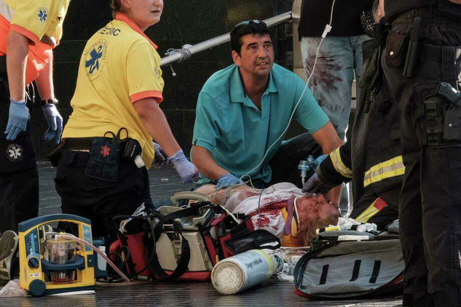 Paramedics tend to one of the many pedestrians struck by a van driving through crowds on Las Ramblas, Barcelona's most famous street, killing at least 12, on Aug. 17, 2017. At least 80 people were injured in what Spanish authorities described as a terrorist attack; two men have been arrested and the Islamic State group has already claimed responsibility. (Sergi Alcazar/El Nacional via The New York Times) -- NO SALES; FOR EDITORIAL USE ONLY WITH STORY SLUGGED BARCELONA-CRASH FOR AUG. 18, 2017. ALL OTHER USE PROHIBITED. —  ORG XMIT: XNYT152 Photo: SERGI ALCAZAR/EL NACIONAL / NYTNS