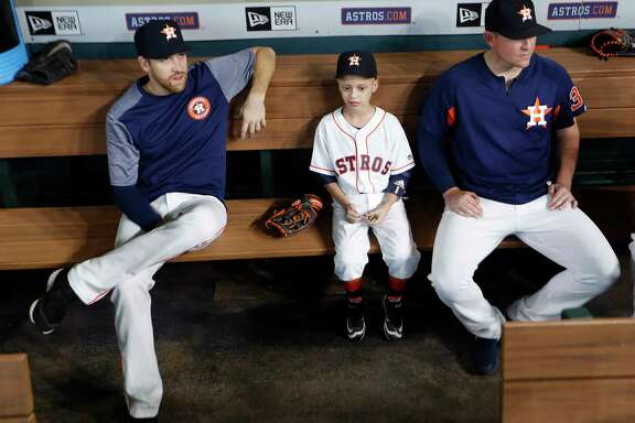 Cameron Gooch, 9, sits in the dugout with Astros pitchers Collin McHugh, left, and Will Harris before the start of the game with the D-Backs at Minute Maid Park on Thursday. Cameron was participating in the Make-A-Wish program.